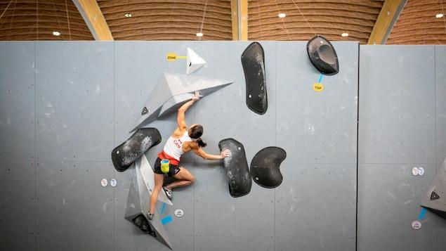 Une femme grimpe sur un mur d'escalade.
