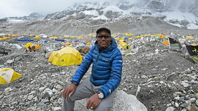 Assis sur un rocher à un camp d'alpinisme, entouré de tentes, il sourit à la caméra.