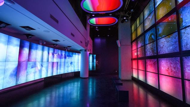 Des murs couverts d'écrans à gauche et à droite de l'image présentent des images d'un nageur canadien dans un éclairage rougeâtre.