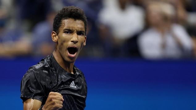 Un joueur de tennis célèbre en serrant le poing