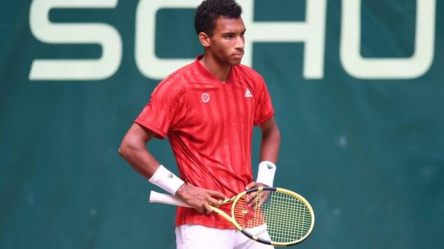 Un joueur de tennis pose ses mains sur ses hanches.