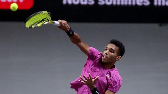 Un joueur de tennis saute pour frapper une balle.