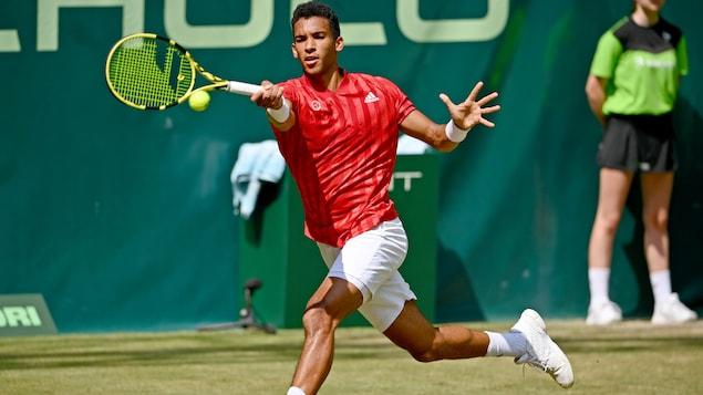 Un joueur de tennis, vêtu d'un chandail rouge et d'un short blanc, s'étire pour frapper une balle du coup droit lors d'un match disputé sur gazon en Allemagne.