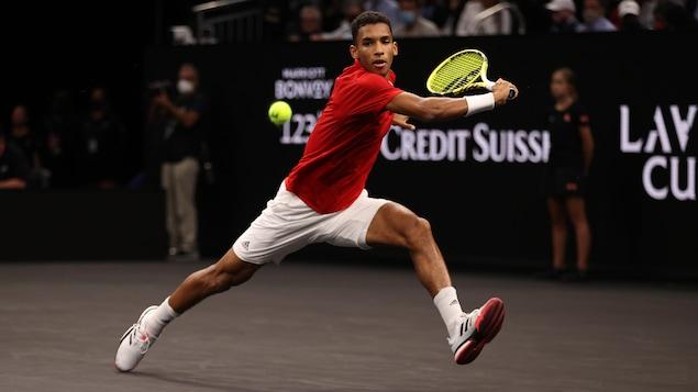Le joueur de tennis plonge pour frapper la balle du revers, d'une main, en fond de terrain.