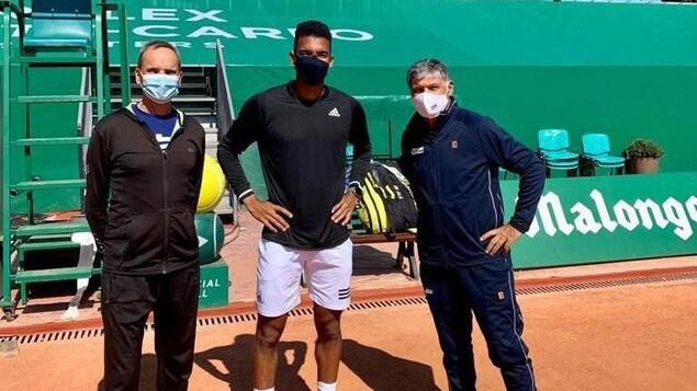 Trois hommes portant le masque prennent la pose sur un terrain de tennis en terre battue.