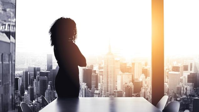 Une femme dans un bureau regarde par une grande fenêtre.