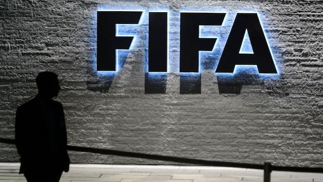 Une silhouette devant le logo de la FIFA.