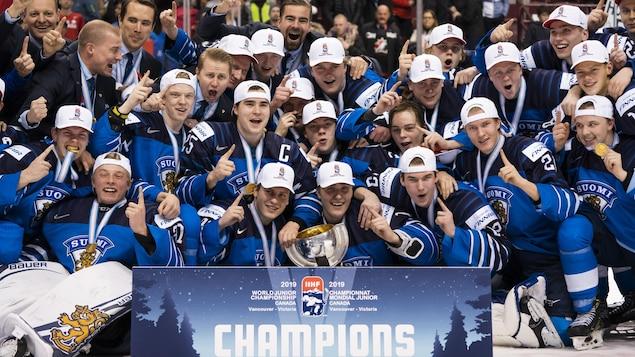 Des joueurs prennent une photo d'équipe avec le trophée qu'ils viennent de gagner.