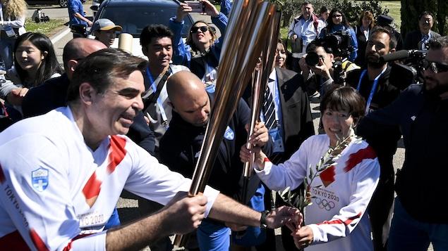 L'ancienne marathonienne japonais, Noguchi Mizuchi, passe la flamme olympique au porte-parole en chef de la Commission européenne, Margaritis Schinas.