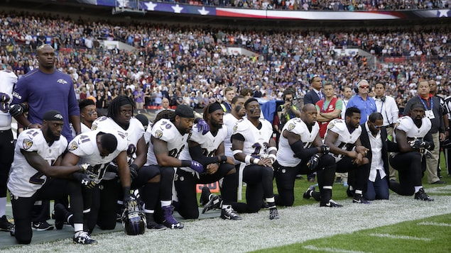 Des joueurs des Ravens de Baltimore et leur ancien coéquipier Ray Lewis (deuxième à partir de la droite) s'agenouillent au cours de l'interprétation de l'hymne national américain.