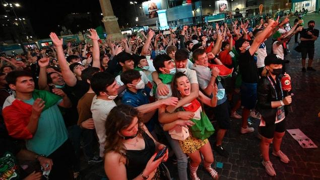 Une foule de monde lève les bras et célèbre la victoire de leur équipe sur la Piazza del Popolo de Rome.