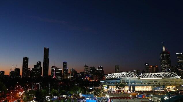 Vue générale du centre-ville de Melbourne le soir, avec un stade éclairé en avant-plan