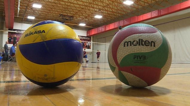 Deux ballons, un Mikasa et un Molten sont un à côté de l'autre sur un terrain de volleyball