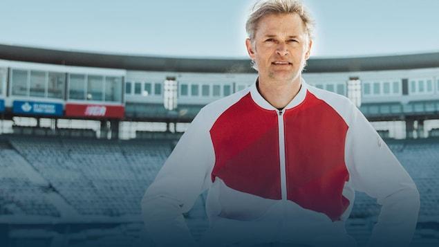 L'entraîneur, assis devant les gradins d'un stade, regarde la caméra.