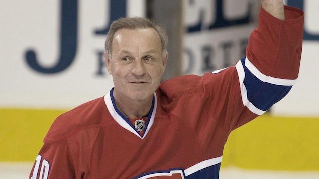 L'ex-hockeyeurs lève le bras gauche pour saluer la foule.