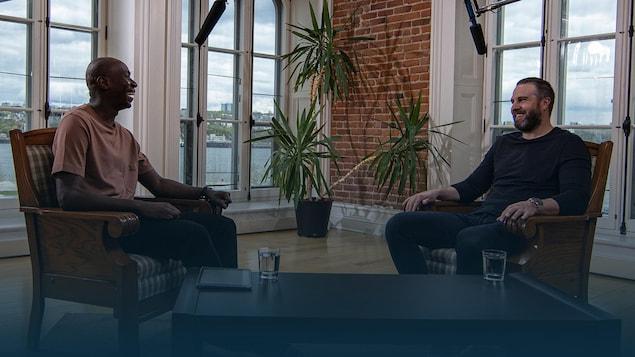 Deux hommes discutent, assis face à face.
