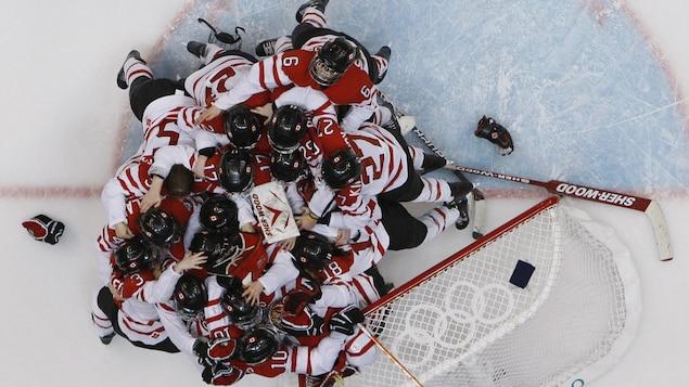 Des joueuses de hockey célèbrent près du filet