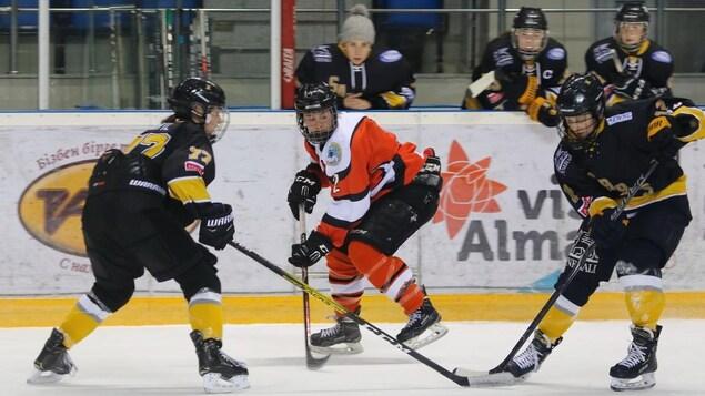 Roxanne Rioux jouant au hockey entourée de joueuses de l'équipe adverse