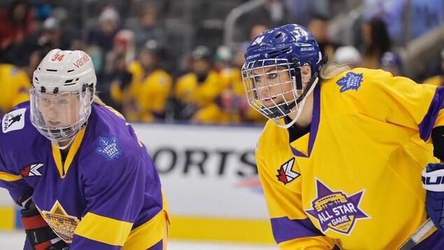 Hannah Miller (à gauche), de l'équipe mauve, et Natalie Spooner, de l'équipe or, attendent la mise au jeu.