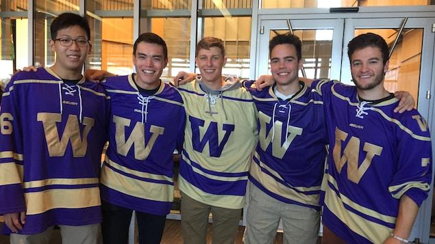 Cinq jeunes hommes posent tout sourire avec des chandails de sports mauve et or sur lesquels il est inscrit la lettre W.