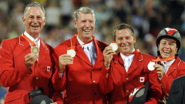 Des cavaliers sourient avec leur médaille.