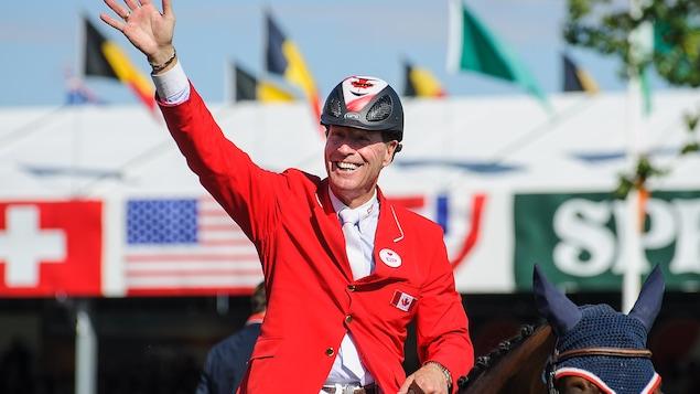 Ian Millar salue la foule de la main sur son cheval