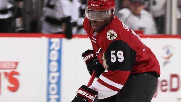 Un joueur de hockey afro-descendant patine.
