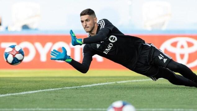 James Pantemis repousse un ballon des mains en plongeant au sol.