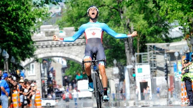 Sur son vélo, il crie et serre les poings à la ligne d'arrivée.