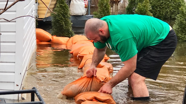 Un homme place un sac de sable sur une digue