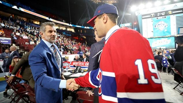 Un dirigeant et un joueur se serrent la main.