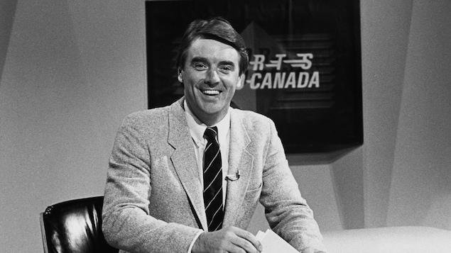 Jean Pagé souriant dans sa jeunesse en veston et cravate à l'animation d'un bulletin de nouvelles sportives.