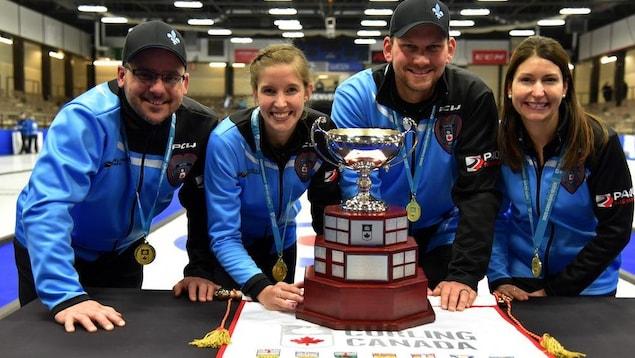 Des joueurs de curling prennent la pose devant un trophée.