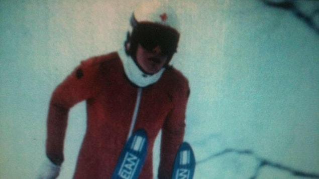 Jean Séguin effectue un saut lors d'une épreuve de saut à ski, dans les années 80.