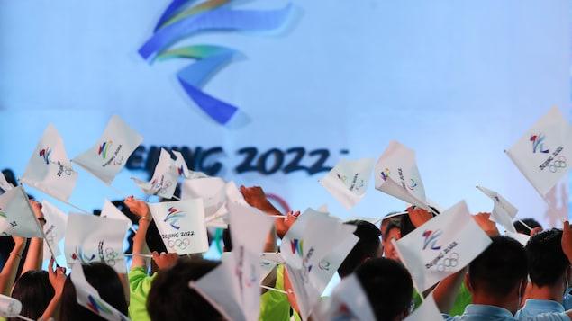 Des spectateurs agitent des drapeaux des jeux olympiques.