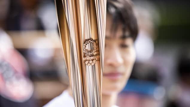 Le flambeau olympique porté par un coureur.