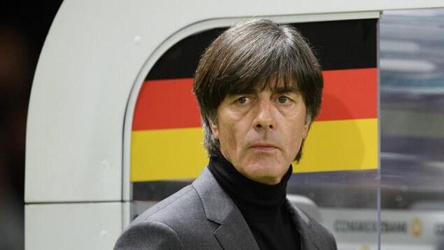 Il surveille le jeu sur le bord du terrain avec derrière lui un drapeau allemand