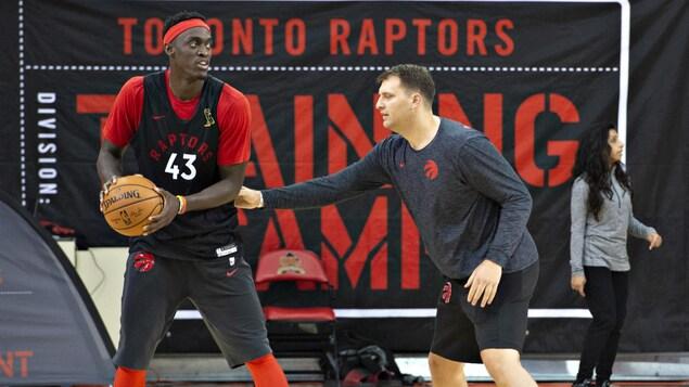 John Corbacio aide Pascal Siakam, des Raptors de Toronto, lors d'une séance d'entraînement.