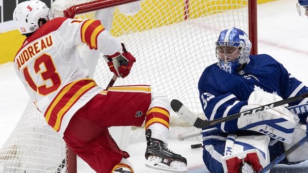 L'attaquant des Flames fait un vol plané alors qu'il voit la rondelle glisser dans le filet des Maple Leafs, derrière le gardien, impuissant.