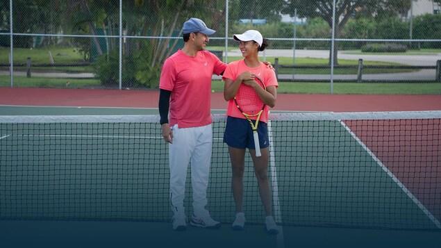 Un père et sa fille, jeune adulte, se regardent sur un court de tennis.