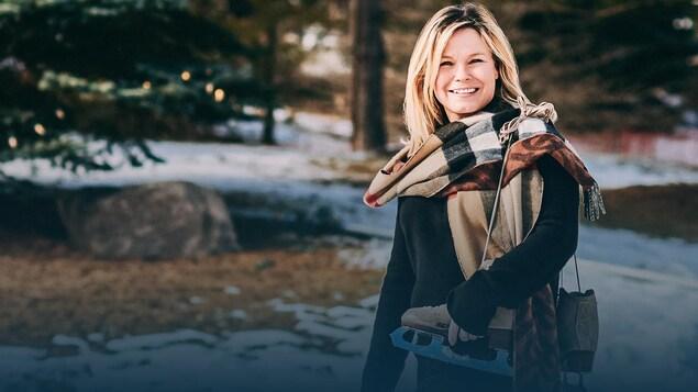 L'ex-patineuse artistique se tient debout et regarde la caméra en souriant.