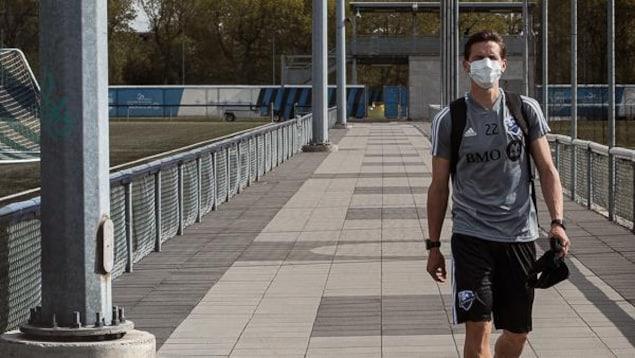 Il marche le long des terrains de soccer.
