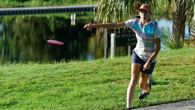Elle effectue un lancer sur un terrain bordé d'un étang.