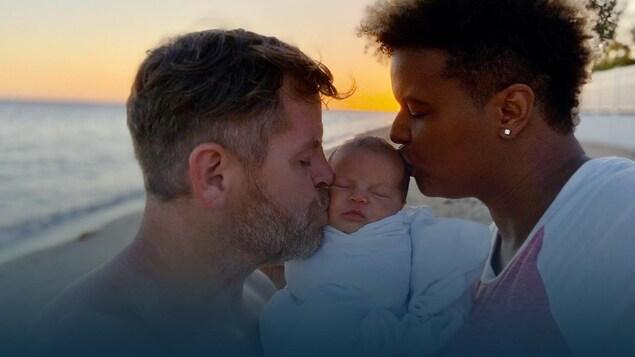 Karina Leblanc et son conjoint Jason embrassent la tête de leur fille Paris devant la mer.