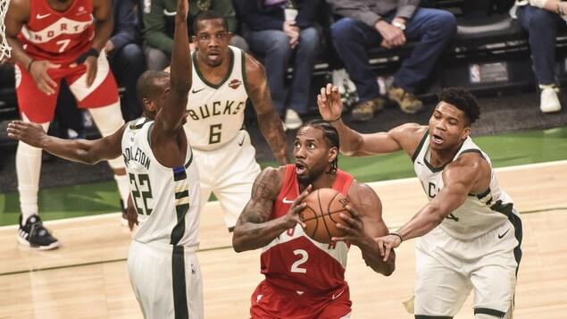 Kawhi Leonard est bien surveillé par deux joueurs des Bucks.