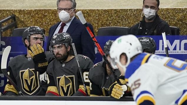 Masqué, il dirige son équipe derrière le banc des joueurs.