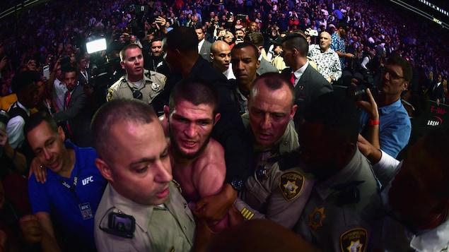 Khabib Nurmagomedov est escorté par des policiers après la mêlée générale qu'il a provoquée lors du gala UFC 229.