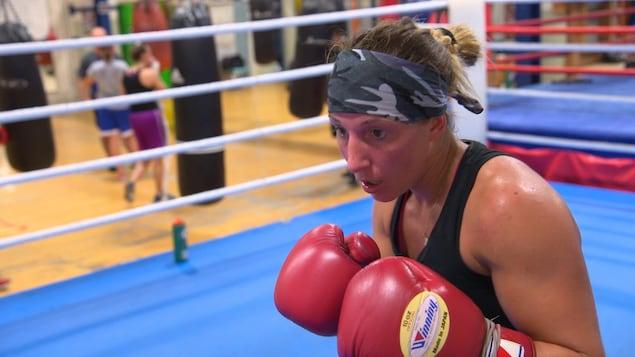 Une boxeuse avec des gants dans un gymnase