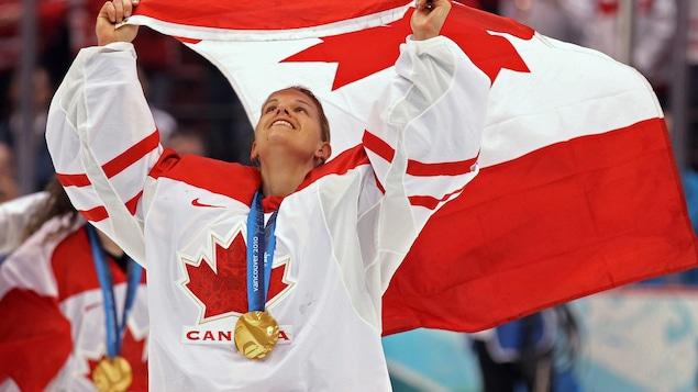 La gardienne de but fait flotter le drapeau canadien au-dessus de sa tête. Elle a une médaille d'or autour du cou.
