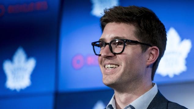Un homme sourit sous le feu des projecteurs lors d'une conférence de presse